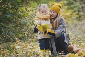 Little blonde girl with her mommy in autumn park, close up