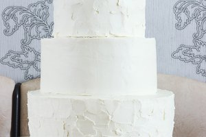 Naked three-tiered cake without ornaments on the table