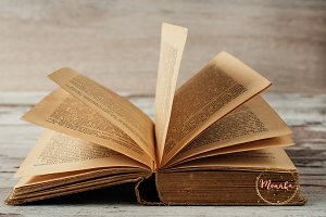 Open old book. Wood background