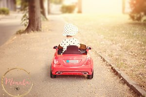 Little girl driving a red car