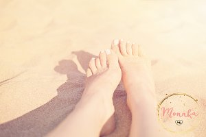 Women feet on the beach