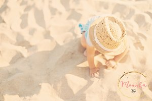 Baby girl playing with the sand