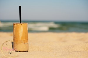 Summer iced coffee on the sand