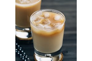 Close-up of a refreshing iced coffee with milk in glasses on a wooden black table.