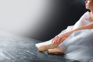 Young ballerina, closeup on legs and shoes, sitting in pointe shooses