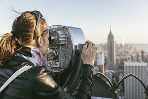 Woman using binoculars in New York.