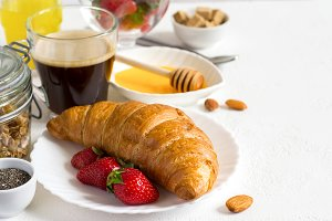 Healthy breakfast set: croissant, berries, and coffee. Selective