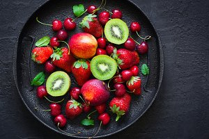 Mix of summer berries and fruits on a black plate. Top view with