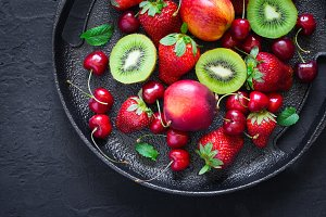 Black dish with different summer berries and fruits. Top view