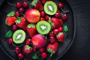 Selection. of summer berries and fruits on a black plate. Top vi