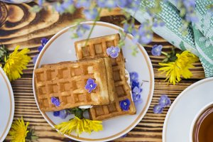 A plate of belgian waffles with and tea cup