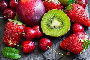 Strawberry, cherry, kiwi and peaches on black slate plate. Long