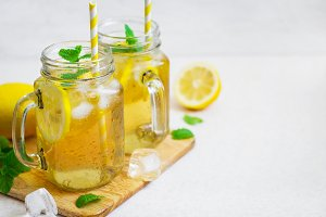 Green ice tea with lemon and mint in a glass jar.