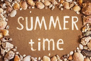 Summer time is written on the sand in frame of sea shells. Trave