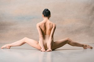 The ballerina is sitting with her back legs wide apart