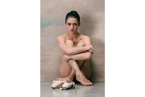 Tired ballet dancer sitting on the wooden floor on a pink background