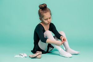 Beautiful little ballerina in black dress for dancing puting on foot pointe shoes