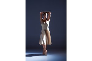 Young beautiful dancer in beige dress dancing on gray background