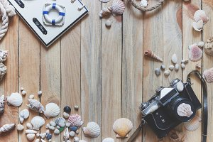 Photo camera and marine decorations on the wooden background