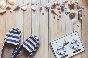 Striped espadrilles and marine decorations on the wooden background