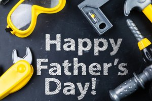 Father's day concept - child tools on black background