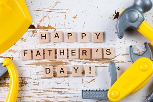Father's day concept - child tools on wood background