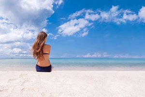 Woman in bikini, enjoy seascape on tropical beach, back view