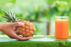 Tropical exotic pineapple fruit woman hand juice