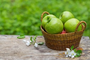Fresh sweet juicy red green apples flowers on wood