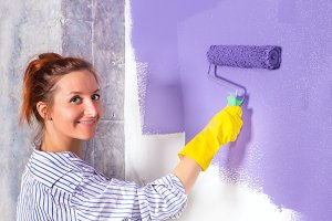 woman paints white wall with purple paint roller