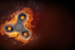 Fidget spinner in fire isolated on black background banner.