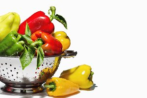 Colander with bright peppers.