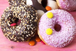 Assortment of colorful donuts with candies on pink wooden background