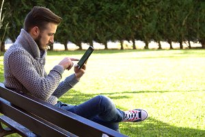 young man sitting in the Park using the tablet