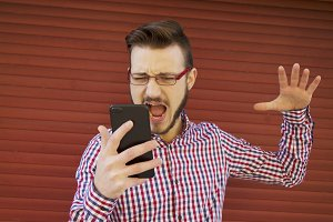 angry hipster man with cellphone