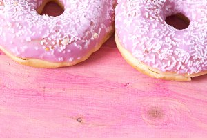 Pink donuts on pink wooden background