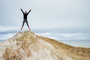 Woman jumping on top of a dune