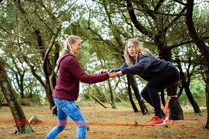 Two friends slacklining in forest