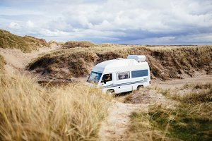 Old camper van between the dunes