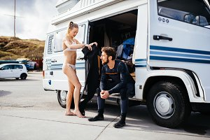 Two surfers in front of camper van