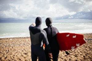 Two surfer friends watching waves
