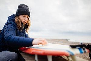 Woman waxing her surf board
