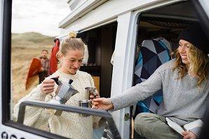 Two friends enjoying coffee at van