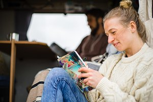 Woman reading book in camper van