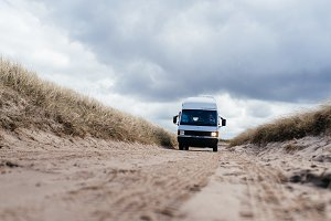 Camper van driving on sandy road