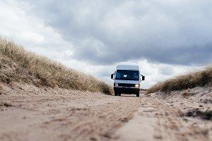 Camper van driving on sandy road