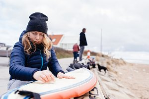 Young woman preparing surf board