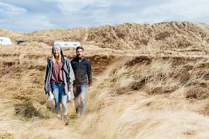 Man and woman walking through dunes