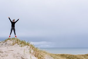 Young woman jumping on a dune