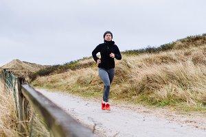 Woman jogging in dune landscape